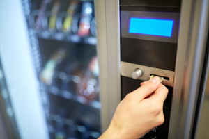 sell, technology, people, finances and consumption concept - hand inserting euro coin to vending machine money slot